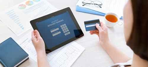 Предпринимательница, пользующаяся кредитной картой для интернет-банкинга